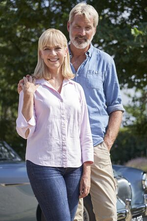 Portrait Of Mature Couple Standing Next To Classic Open Top Sports Car