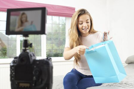 Teenage Female Vlogger Recording Broadcast At Home Stock Photo
