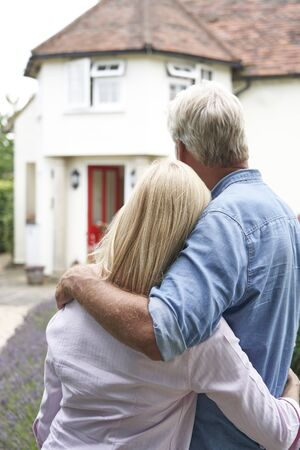 Rear View Of Mature Couple Standing In Garden Look At Dream Home In Countryside