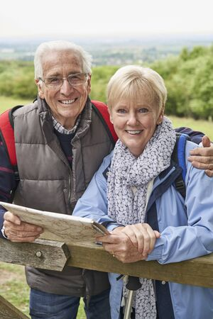 Portrait Of Retired Couple On Walking Holiday Resting On Gate With Map