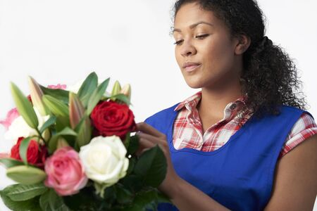 Female Florist Arranging Bouquet Of Lillies And Roses Against White Background