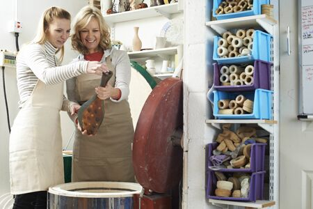 Tutor With Female Student In Pottery Studio Firing Vase In Kiln