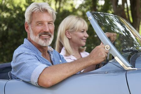 Mature Couple Enjoying Road Trip In Classic Open Top Sports Car Together Stock Photo