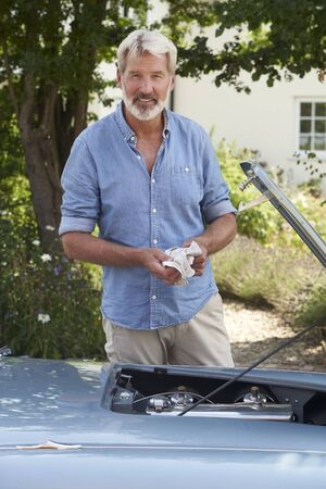 Portrait Of Mature Man Working On Engine Under Hood Of  Restored Classic Sports Car Outdoors