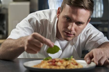 Male Chef Garnishing Plate Of Food In Professional Kitchen
