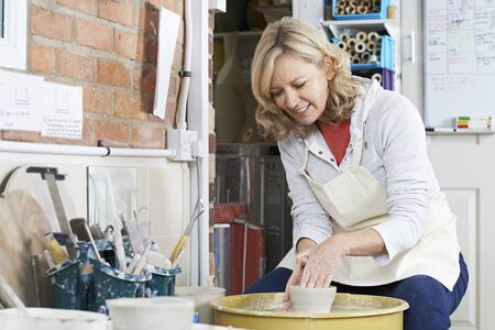 Mature Woman Working At Potters Wheel In Studio