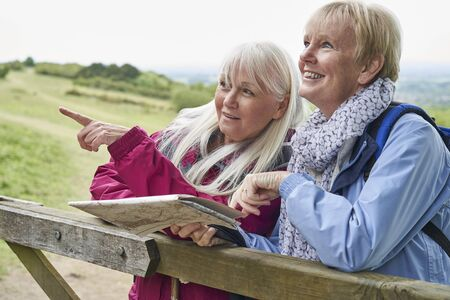 Two Senior Women Friends On Walking Holiday Resting On Gate With Map