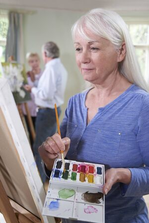 Senior Woman Attending Painting Class With Teacher In Background