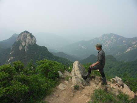 a man stand at mountain Peak
