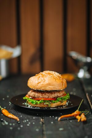 True Classic burger on a dark wooden background with green vegetables and salad. Horizontal format