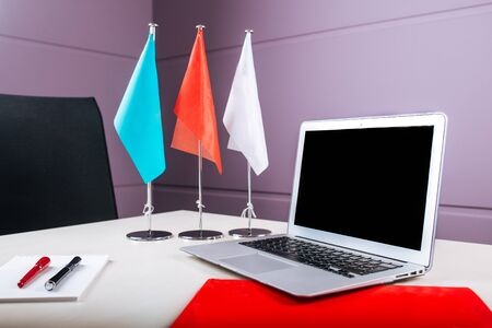 Light bright office workplace with a silver laptop, notebook, pens and different flags on the table, horizontal