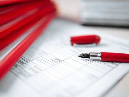 Closeup on a paper report red pen working place office, horizontal