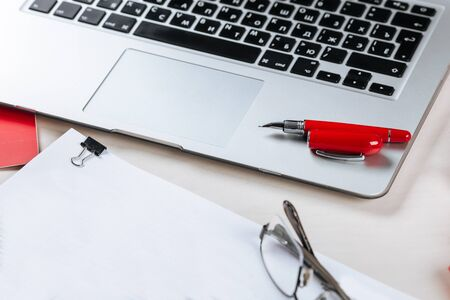 Top view on office workplace with a silver laptop, papers and reports, red pen glasses on the table, horizontal