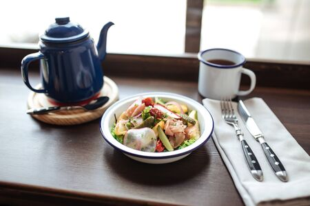 Healthy appetizing gourmet salad with vegetables smoked fish and pickles on the wooden table with coffee and kettle, horizontal