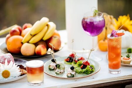summer catering buffet with canap snacks with eggplant, olives, herbs, tomatoes and meat. On a white wooden table. Horizontal view. With cocktails and fruits