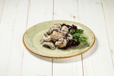 Appetizing cooked mushrooms with sauce on the white wooden bakcground, horizontal