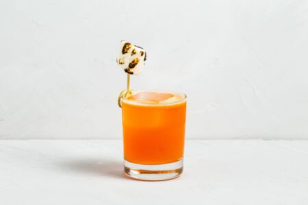 Sweet orange fruit delicious cocktail decorated with singed marshmallow in a glass on the white background, horizontal