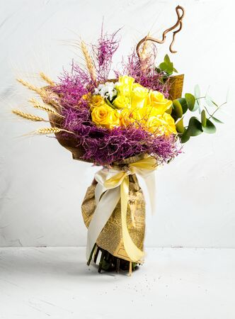 Beautiful nice bouquet in a rustic style with wheat and yellow roses on the white background, vertical