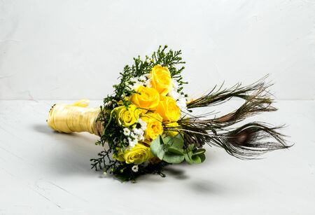 Beautiful fresh light bouquet of yellow roses flowers with peacock feathers on a white background