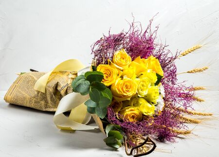 Beautiful nice bouquet in a rustic style with wheat and yellow roses on the white background, horizontal 免版税图像