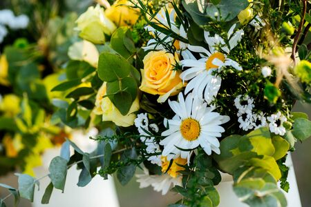 Closeup on rustic beautiful fresh bouquet with yellow roses and daisies, horizontal