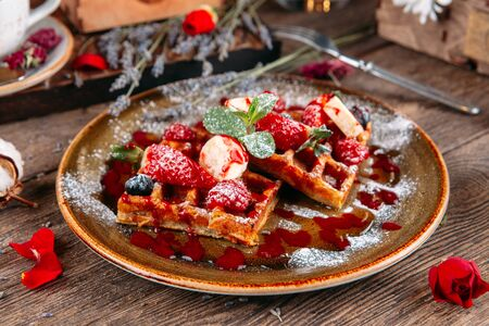 Appetizing sweet dessert Belgian waffles with berries and sauce, horizontal