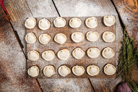 Top view on semi-finished homemade dumplings pelmeni laid out on a wooden board sprinkled with flour, horizontal