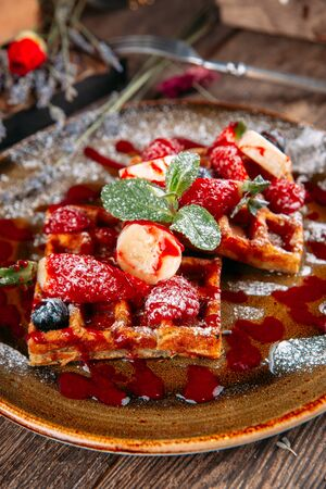 Appetizing sweet dessert Belgian waffles with berries and sauce, vertical Фото со стока