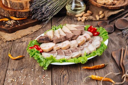 Kazakh national traditional dish horse sausage kazy on the wooden background, horizontal