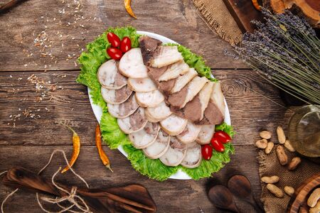 Top view on kazakh national traditional dish horse sausage kazy on the wooden background, horizontal