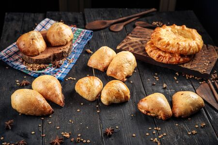 Middle Eastern Cuisine Asian Baked Samsa Pies on the dark wooden background horizontal Stock Photo