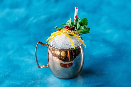 Alcohol tropical cocktail with crushed ice orange peel and mint garnish in a copper mug on the blue background, horizontal Stock Photo