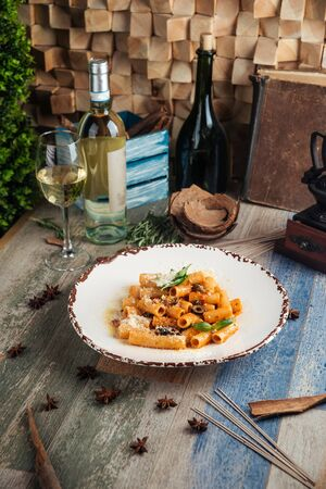 Closeup on italian dish rigatoni pasta putanesca with olives anchovies, vertical Banque d'images