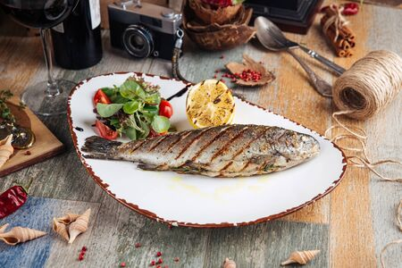 Grilled trout fish with salad and lemon on the wodoen table, horizontal