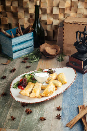 Assorted puff pastry pies pirozhki on the wooden table, vertical