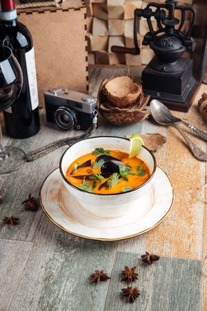 Appetizing seafood tom yam soup on the wooden table, vertical Stock Photo