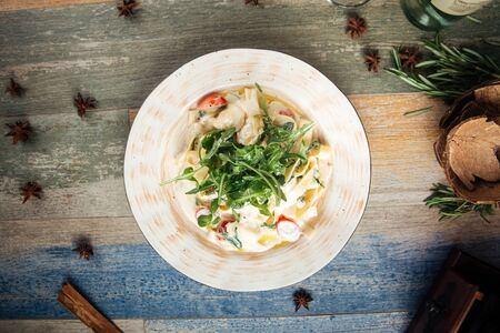 Top view on fettuccine alfredo with arugula and cherry tomatoes, horizontal Banque d'images