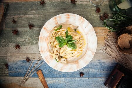 Top view on tagliatelle pasta with mushrooms in a creamy sauce with parmesan and white wine, horizontal