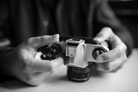 Man's hands set up retro film camera. Black and white. Horizontal
