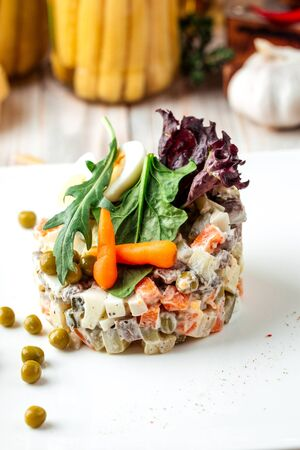 Gourmet served olivier russian salad dressed with mayonnaise, vertical
