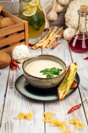 Gourmet potato soup with cream and smoked horsemeat, vertical