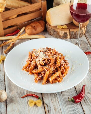 Closeup on italian penne pasta bolognese with beef and parmesan, vertical