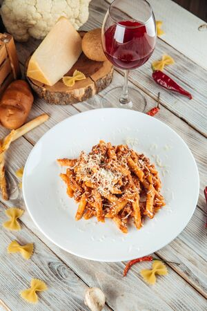 Italian penne pasta bolognese with beef and parmesan, vertical
