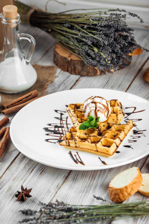 Belgian waffles poured with ice cream and chocolate syrup, vertical Stockfoto