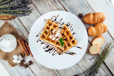 Top view on belgian waffles poured with ice cream and chocolate syrup, horizontal