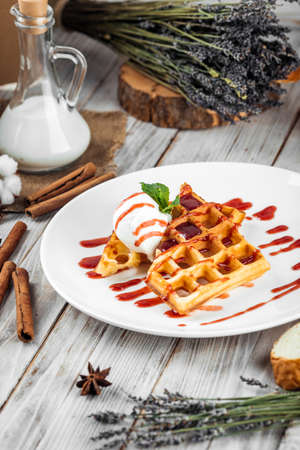 Belgian waffles poured with ice cream and berry syrup, vertical