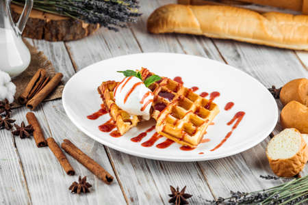 Belgian waffles poured with ice cream and berry syrup, horizontal