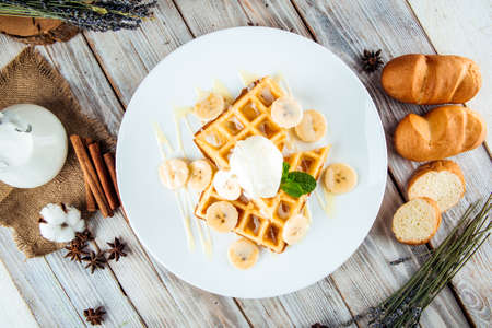 Top view on belgian waffles poured with ice cream and banana syrup, horizontal