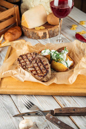 Beef steak with baked potatoes  sour cream and pepper sauce, vertical