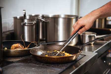 Restaurant chef cooking black pasta spaghetti in a pan with tongs